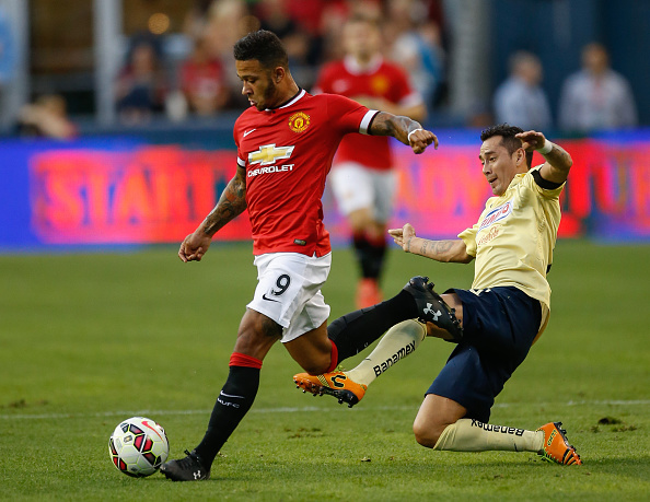 SEATTLE, WA - JULY 17:  Memphis Depay #9 of Manchester United dribbles against Rubens Sambueza #14 of Club America during the International Champions Cup at CenturyLink Field on July 17, 2015 in Seattle, Washington. Manchester United defeated Club America 1-0.  (Photo by Otto Greule Jr/Bongarts/Getty Images)