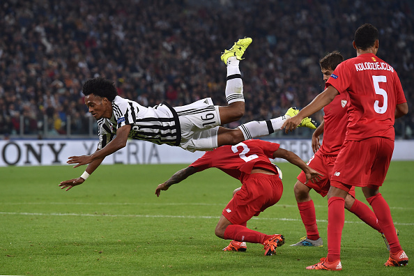 TURIN, ITALY - SEPTEMBER 30:  Juan Cuadrado (L) of Juventus is tackled by Benoit Tremoulinas of Sevilla during the UEFA Champions League group E match between Juventus and Sevilla FC on September 30, 2015 in Turin, Italy.  (Photo by Valerio Pennicino/Getty Images)