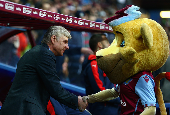 BIRMINGHAM, ENGLAND - DECEMBER 13:  Arsene Wenger of Arsenal is greeted by the Villa mascot prior to the Barclays Premier League match between Aston Villa and Arsenal at Villa Park on December 13, 2015 in Birmingham, England.  (Photo by Clive Mason/Getty Images)