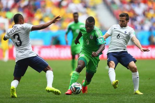 BRASILIA, BRAZIL - JUNE 30:  Emmanuel Emenike of Nigeria is challenged by Patrice Evra (L) and Yohan Cabaye of France during the 2014 FIFA World Cup Brazil Round of 16 match between France and Nigeria at Estadio Nacional on June 30, 2014 in Brasilia, Brazil.  (Photo by Jeff Gross/Getty Images)