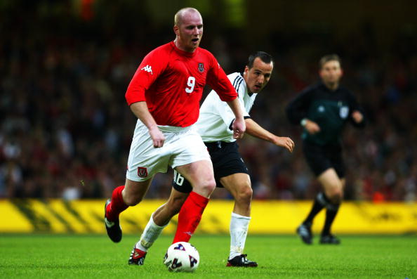 CARDIFF - MAY 14:  John Hartson of Wales takes the ball past Jens Jeremies of Germany during the International Friendly match played at the Millennium Stadium, in Cardiff, Wales on May 14, 2002. Wales won the match 1-0. DIGITAL IMAGE. (Photo by Ben Radford/Getty Images)