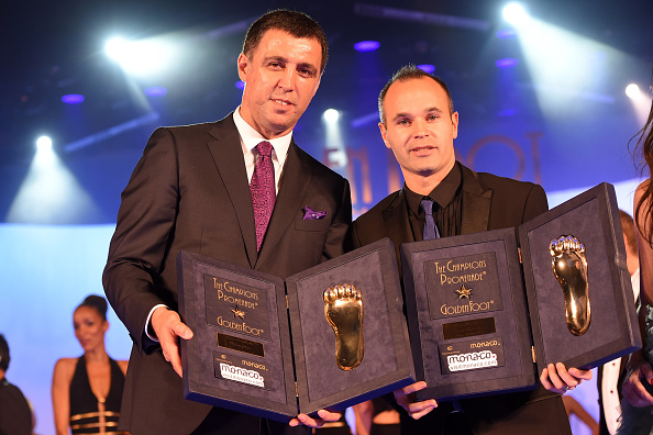 MONTE-CARLO, MONACO - OCTOBER 13:  Hakan Sukur (L) and Andres Iniesta receive the Golden Foot Award trophy during the Golden Foot Award 2014 ceremony at Sporting Club on October 13, 2014 in Monte-Carlo, Monaco.  (Photo by Valerio Pennicino/Getty Images for Golden Foot)