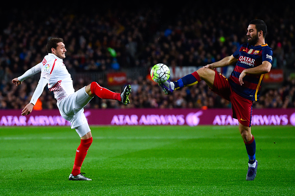BARCELONA, SPAIN - FEBRUARY 28: Arda Turan of FC Barcelona competes for the ball with Sebastian Cristoforo of Sevilla FC during the La Liga match between FC Barcelona and Sevilla FC at Camp Nou on February 28, 2016 in Barcelona, Spain.  (Photo by David Ramos/Getty Images)