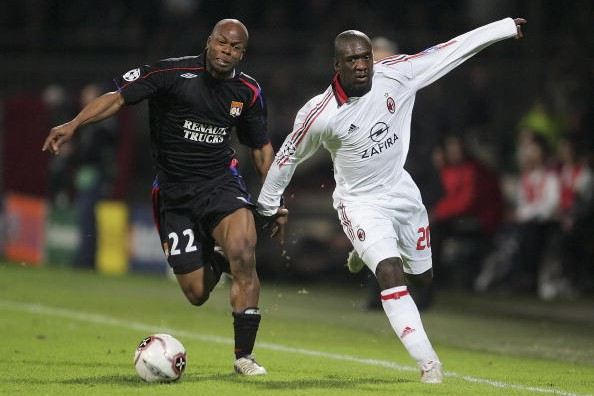 LYON, FRANCE - MARCH 29:  Sylvain Wiltord of Lyon battles with Clarence Seedorf of AC Milan during the UEFA Champions League Quarter Final First Leg match between Lyon and AC Milan at the Stade de Gerland on March 29, 2006 in Lyon, France.  (Photo by Julian Finney/Getty Images)