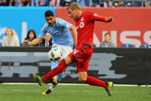 NEW YORK, NY - MARCH 13:  David Villa #7 of New York City FC kicks the ball past Damien Perquis #24 of Toronto FCat Yankee Stadium on March 13, 2016 in the Bronx borough of New York City.  (Photo by Mike Stobe/Getty Images)