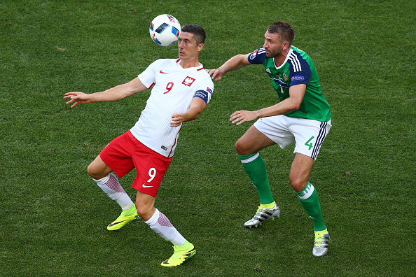 NICE, FRANCE - JUNE 12: Robert Lewandowski of Poland controls the ball under pressure of Gareth McAuley of Northern Ireland during the UEFA EURO 2016 Group C match between Poland and Northern Ireland at Allianz Riviera Stadium on June 12, 2016 in Nice, France.  (Photo by Alex Livesey/Getty Images)