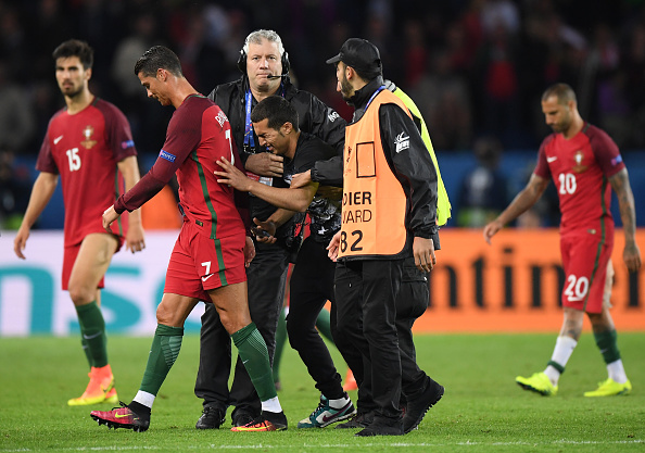 PARIS, FRANCE - JUNE 18:  Stewards carry an emotional fan off the pitch as he attempts to reach Cristiano Ronaldo of Portugal during the UEFA EURO 2016 Group F match between Portugal and Austria at Parc des Princes on June 18, 2016 in Paris, France.  (Photo by Matthias Hangst/Getty Images)