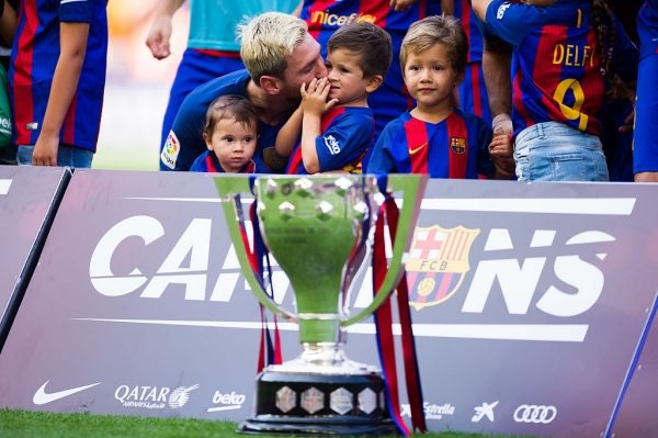 BARCELONA, SPAIN - AUGUST 20: Lionel Messi of FC Barcelona kisses his son Thiago Messi as they pose with the Spanish La Liga 2015-2016 trophy before the La Liga match between FC Barcelona and Real Betis Balompie at Camp Nou on August 20, 2016 in Barcelona, Spain. (Photo by Alex Caparros/Getty Images)