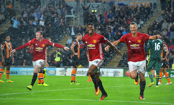 HULL, ENGLAND - AUGUST 27: Marcus Rashford of Manchester United (C) celebrates scoring his sides first goal with team mates (L) Wayne Rooney of Manchester United and (R) Zlatan Ibrahimovic of Manchester United during the Premier League match between Hull City and Manchester United at KCOM Stadium on August 27, 2016 in Hull, England.  (Photo by Mark Runnacles/Getty Images)