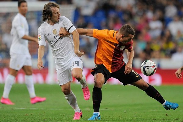 MADRID, SPAIN - AUGUST 18:  Lukas Podolski of Galatasaray fends off Luka Modric of Real Madrid during the Santiago Bernabeu Trophy match between Real Madrid and Galatasaray at Estadio Santiago Bernabeu on August 18, 2015 in Madrid, Spain.  (Photo by Denis Doyle/Getty Images)
