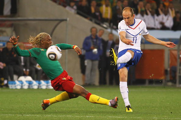 CAPE TOWN, SOUTH AFRICA - JUNE 24:  Arjen Robben of the Netherlands shoots past the diving challenge of Rigobert Song of Cameroon during the 2010 FIFA World Cup South Africa Group E match between Cameroon and Netherlands at Green Point Stadium on June 24, 2010 in Cape Town, South Africa.  (Photo by Lars Baron/Getty Images)