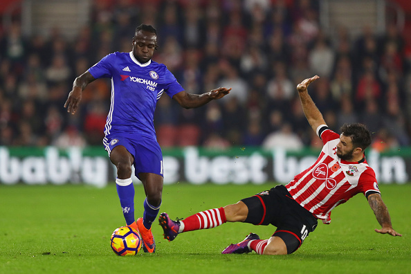 SOUTHAMPTON, ENGLAND - OCTOBER 30: Victor Moses of Chelsea (L) is tackled by Charlie Austin of Southampton (R) during the Premier League match between Southampton and Chelsea at St Mary's Stadium on October 30, 2016 in Southampton, England.  (Photo by Clive Rose/Getty Images)