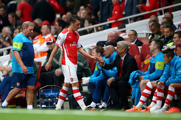 LONDON, ENGLAND - OCTOBER 01:  Mesut Oezil of Arsenal shakes hands with Arsene Wenger, manager of Arsenal after being substituted during the UEFA Champions League group D match between Arsenal FC and Galatasaray AS at Emirates Stadium on October 1, 2014 in London, United Kingdom.  (Photo by Paul Gilham/Getty Images)